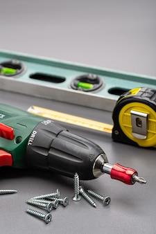 Śrubokręt, poziomica, taśma miernicza i śruby na szarej powierzchni