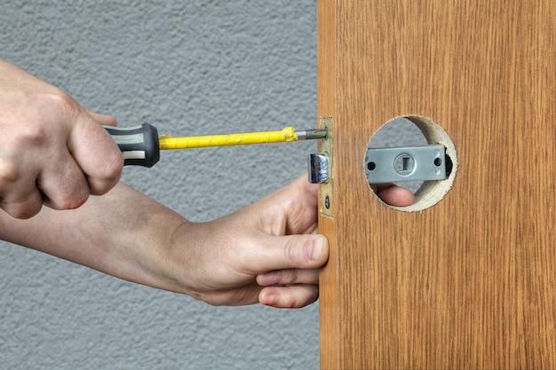 Śrubokręt w rękach ślusarza z bliska, wymiana zamka w drzwiach wewnętrznych.