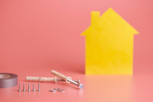 Śruby i żółta figura w kształcie domku na różowej powierzchni