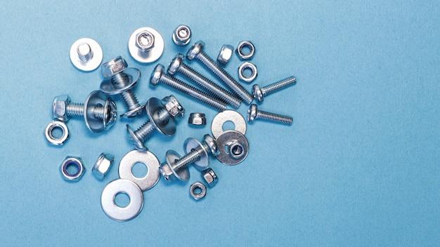 Śruby, nakrętki i podkładki różnych rozmiarów na niebieskim tle.