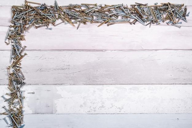 Śruby o różnych kształtach u góry i z boku wolnej przestrzeni na drewnianym tle. widok z góry z miejscem na tekst