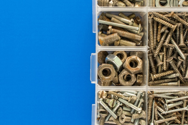 Śruby, śruby, nakrętki i inne rzeczy stolarskie w plastikowej skrzynce narzędziowej (organizator sprzętu). płaski świecki widok z góry z miejsce na tekst. zdjęcie stockowe.