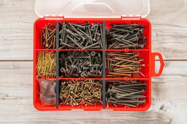 Śruby, śruby, nakrętki i inne rzeczy stolarskie w plastikowej skrzynce narzędziowej (organizator sprzętu). płaski widok z góry. zdjęcie stockowe.