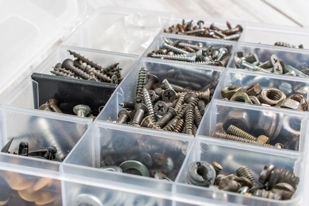 Śruby, śruby, nakrętki i inne rzeczy stolarskie w plastikowej skrzynce narzędziowej (organizator sprzętu). zdjęcie stockowe.