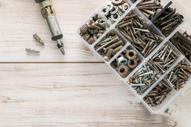 Śruby, śruby, nakrętki i inne rzeczy stolarskie w plastikowej skrzynce narzędziowej (organizatorze sprzętu) ze śrubokrętem. płaski świecki widok z góry z miejsce na tekst. zdjęcie stockowe.