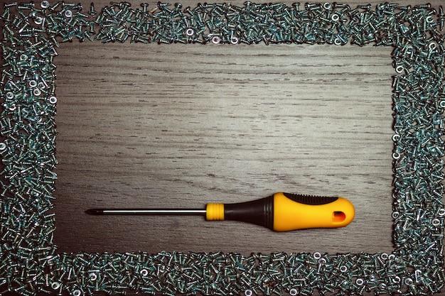 Śruby z śrubokrętem na drewnianym tle.