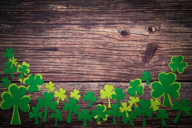 St patricks dzień, złote monety, świąteczny kapelusz i zieleni shamrocks na drewnianym