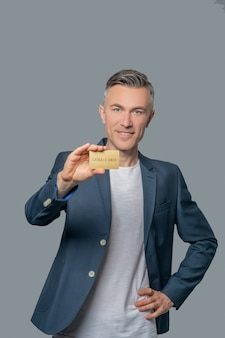 Stabilność. radosny pewny siebie mężczyzna w ciemnej biznesowej kurtce pokazujący złotą kartę bankową na szarym tle