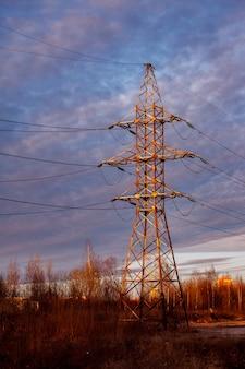 Stacja dystrybucji energii. wieża przesyłowa wysokiego napięcia. linia wysokiego napięcia o zachodzie słońca. moc wysokiego napięcia i kolorowe niebo. wieże nadawcze