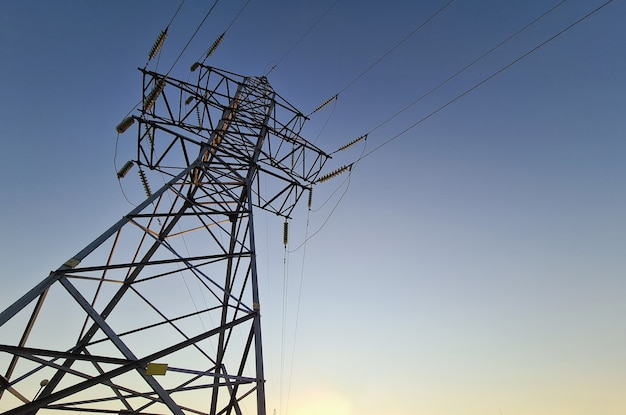 Stacja elektryczna z przewodami stojącymi na tle zbliżenia zachodu słońca