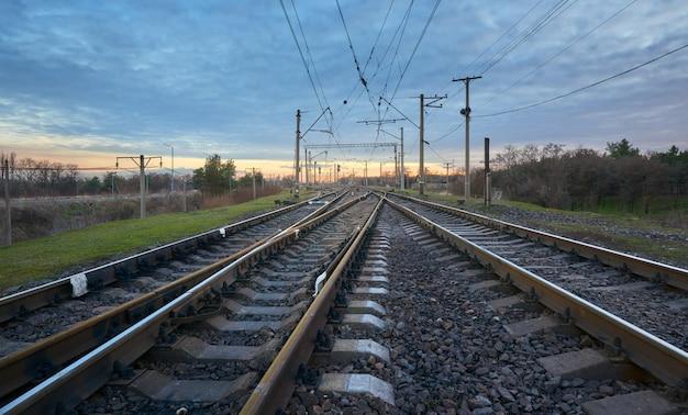 Stacja kolejowa przeciw pięknemu niebu przy zmierzchem. popędzać