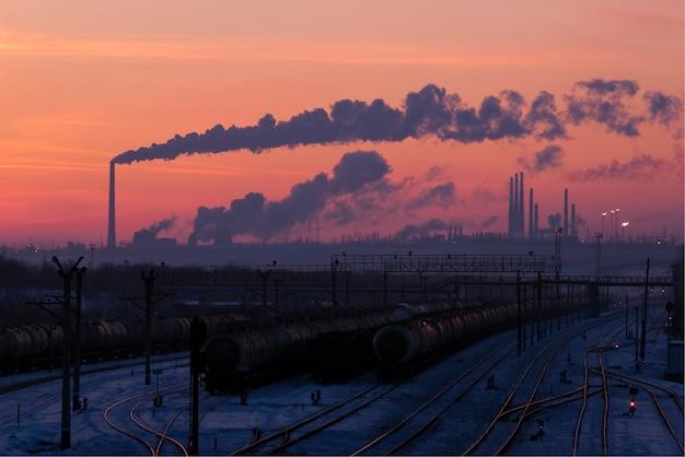 Stacja kolejowa. przedsiębiorstwo przemysłowe na horyzoncie. zachód słońca.