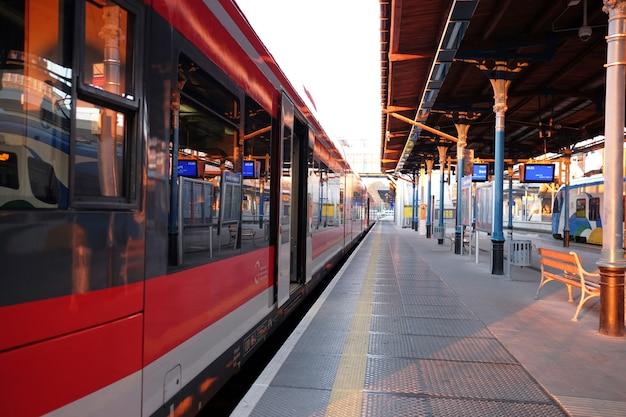Stacja kolejowa z pociągami w świetle słońca lub wschodu słońca