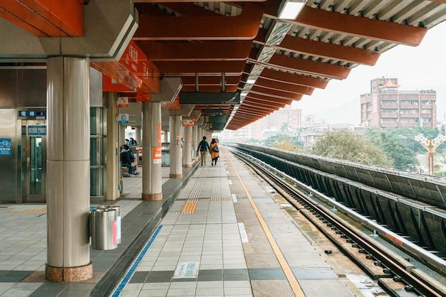Stacja metra taipei beitou z ludźmi czekającymi na peronie na pociąg. transport publiczny. współczesna architektura z kulturalnym designem.