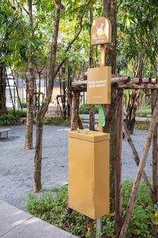 Stacja na odpady dla zwierząt w parku, kosz na psie odchody i pojemnik z plastikowymi workami na śmieci.