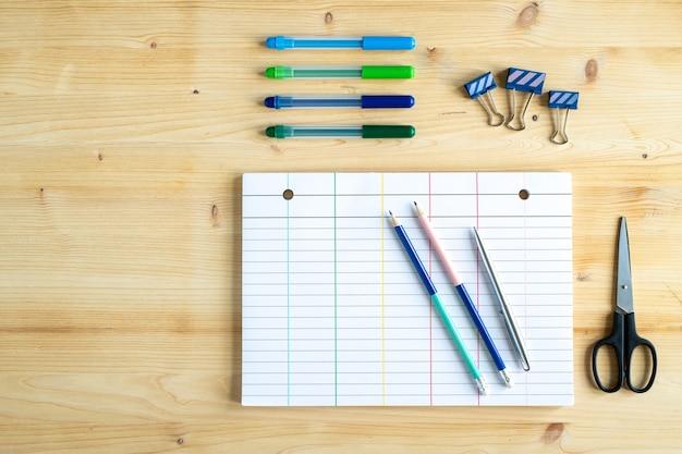 Stacjonarne artykuły biurowe na drewnianym stole - spinacze, nożyczki, czysty zeszyt, ołówki, długopis i zakreślacze
