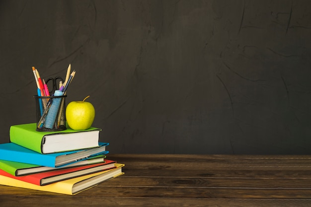 Stacjonarne i jabłko na stos książek na stole