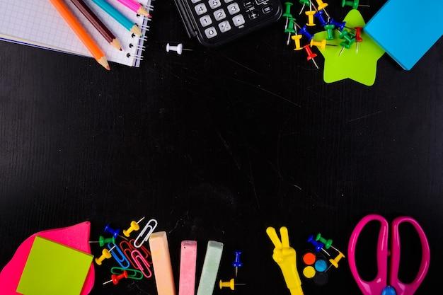 Stacjonarne ołówki kredowe szpilki kalkulator nożyczki itp. na czarnym tle pośrodku