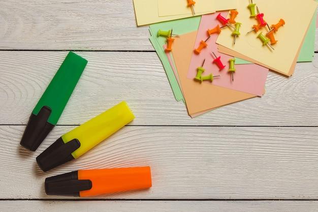 Stacjonarne, pinezki na naklejkach, kolorowe markery, zakreślacze na białym drewnianym stole. koncepcja planowania biznesowego.