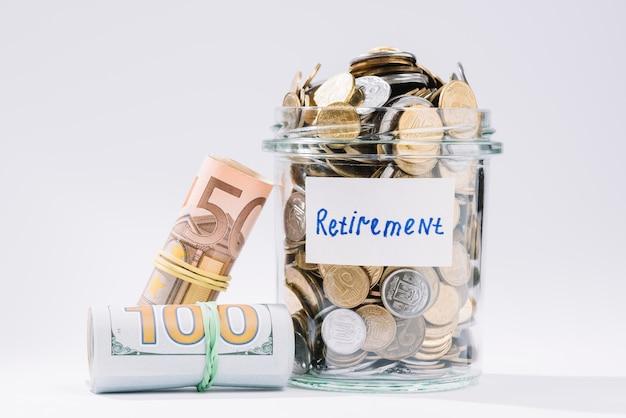 Staczający się w górę banknotów i emerytura zbiornika pełno monety na białym tle