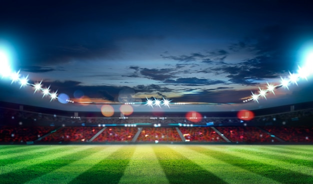 Stadion piłkarski z oświetleniem, zieloną trawą i nocnym niebem