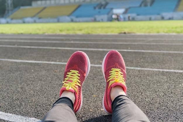 Stadion toru tło, bieżnia kobiece nogi w trampki