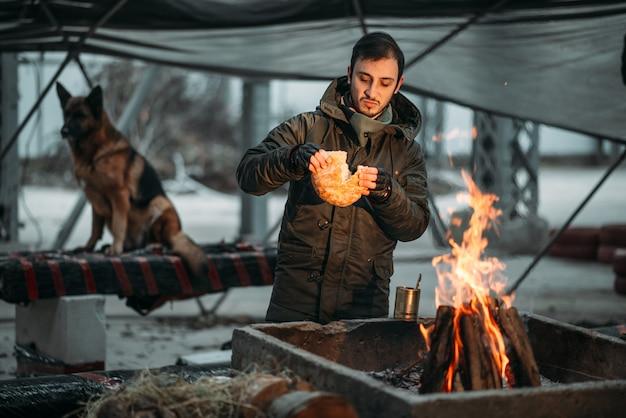 Stalker gotuje jedzenie w ogniu. postapokaliptyczny styl życia na ruinach, dzień zagłady, dzień sądu