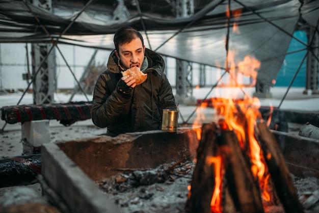 Stalker, mężczyzna jedzenie przed kominkiem. postapokaliptyczny styl życia, dzień zagłady, horror wojny nuklearnej