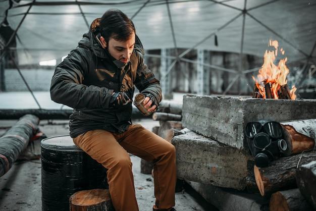 Stalker, mężczyzna jedzenie przed kominkiem