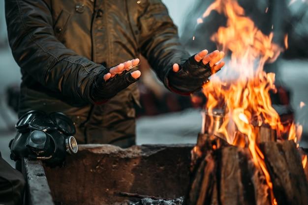 Stalker, mężczyzna, ogrzewa ręce w ogniu. postapokaliptyczny styl życia z maską gazową, koniec świata,