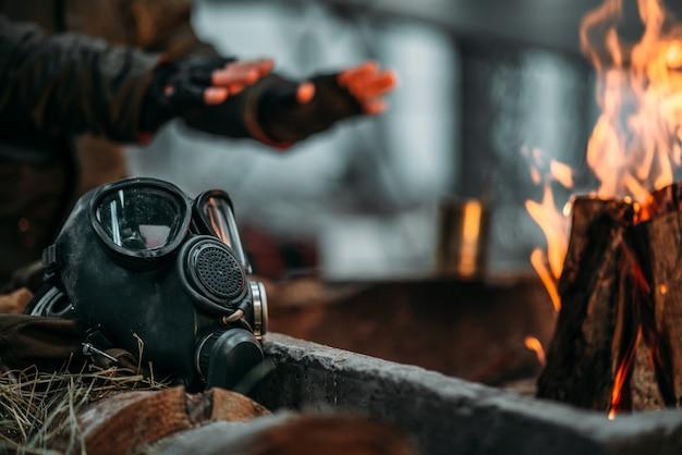 Stalker, mężczyzna, ogrzewa ręce w ogniu