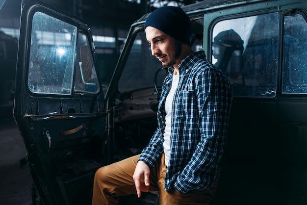 Stalker, samotny podróżnik przeciwko opuszczonemu samochodowi, stara fabryka wojskowa.