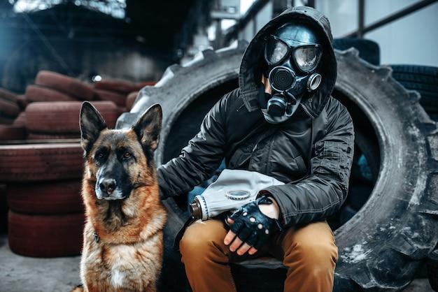 Stalker w masce gazowej i psie, przyjaciele w postapokaliptycznym świecie. postapokalipsa na ruinach, dzień zagłady, dzień sądu