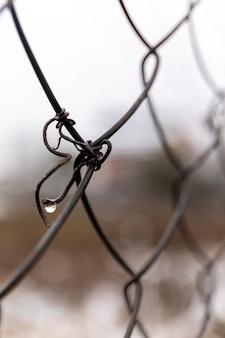 Stalowa siatka. detal z metalowego ogrodzenia. abstrakcyjne pojęcie. nieostrość.