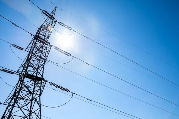 Stalowa wieża wysokiego napięcia energii elektrycznej przed blaskiem słońca i jasnego nieba.
