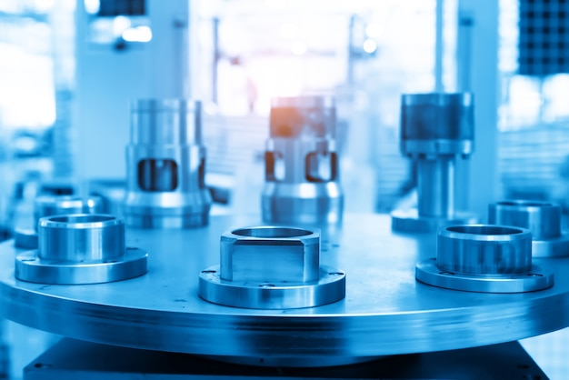Stalowe części cylindryczne znajdują się na platformie maszyny