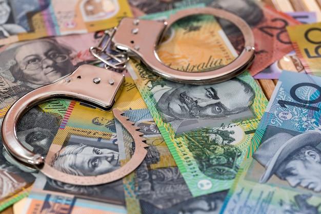 Stalowe kajdanki na tle dolarów australijskich z bliska