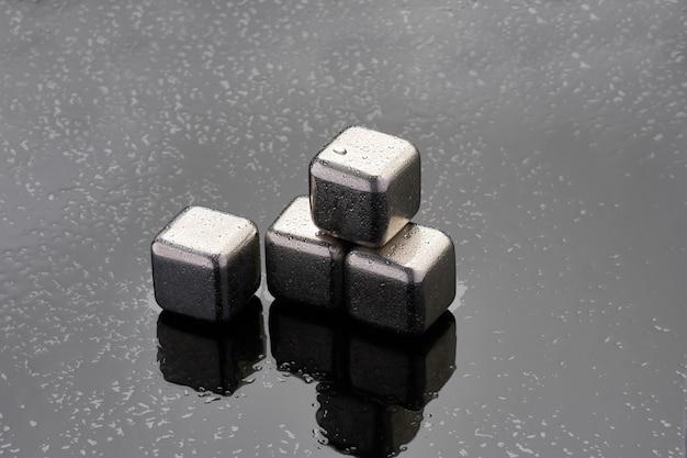 Stalowe kostki chłodzące do napojów koktajlowych na szklanej powierzchni