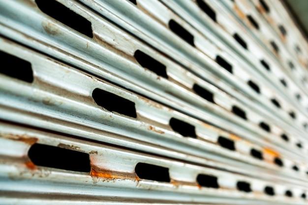Stalowe rustykalne rocznika toczenia drzwi z otworami. rustykalne tekstury drzwi migawki.