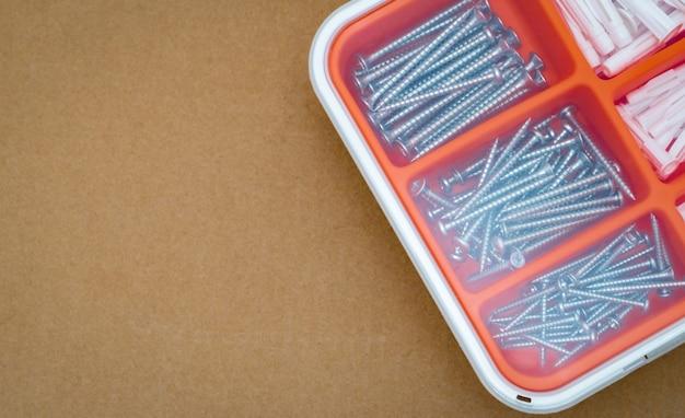 Stalowe srebrne śruby i kołek rozporowy w pomarańczowym plastikowym pudełku. skrzynka narzędziowa widok z góry na tle brązowego pola papieru z miejsca na kopię. zestaw wkrętów i plastikowych kołków do wiercenia w ścianie i elementów montażowych.