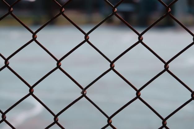 Stalowego drutu sieci ogrodzenie z zamazanym zielonym tłem