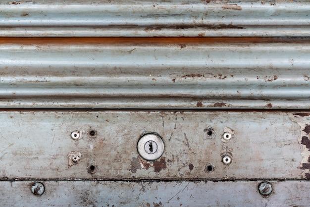 Stalowy nieociosany rocznika toczny drzwi z keyhole. rustykalne tekstury drzwi migawki.