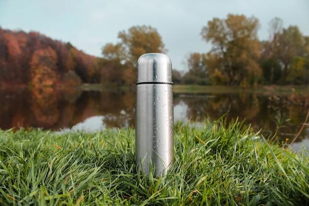 Stalowy termos próżniowy na zielonej trawie, jesiennym lesie i jeziorze.