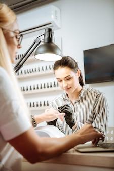 Stały klient. młoda obiecująca stylistka paznokci obsługująca swojego stałego klienta w salonie kosmetycznym
