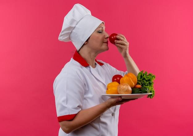 Stały widok profilu kobiet w średnim wieku kucharz w mundurze szefa kuchni trzymając warzywa na talerzu wąchając pomidora w dłoni