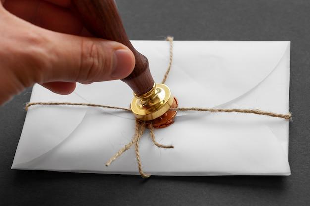 Stamper wosku notarialnego. biała koperta z brązową pieczęcią lakową, złoty znaczek. elastyczny design, płaskie ułożenie. martwa natura z akcesoriami pocztowymi.