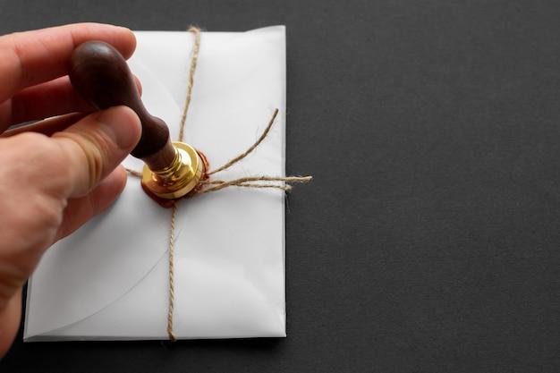 Stamper wosku notarialnego. biała koperta z brązową pieczęcią lakową, złoty znaczek. martwa natura z akcesoriami pocztowymi. kopiuj przestrzeń.
