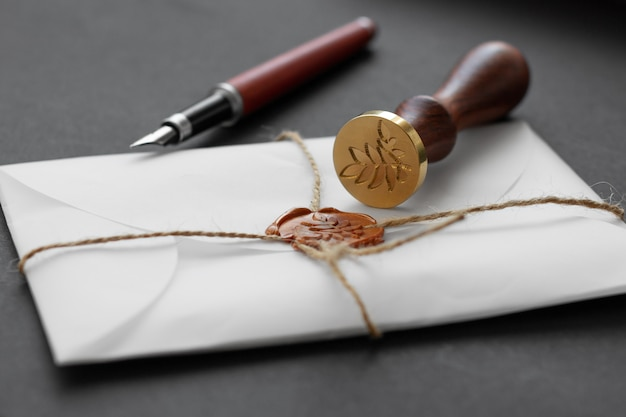 Stamper wosku notarialnego. biała koperta z brązową pieczęcią lakową, złoty znaczek. martwa natura z akcesoriami pocztowymi.