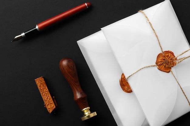 Stamper wosku notarialnego. biała koperta z brązową pieczęcią lakową, złoty znaczek. responsywne wzornictwo, płaskie ułożenie. martwa natura z akcesoriami pocztowymi.