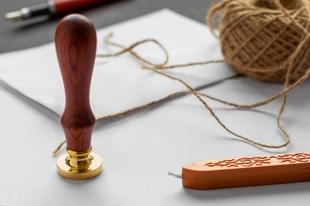 Stamper wosku notarialnego. biała koperta z brązową pieczęcią lakową, złoty znaczek.